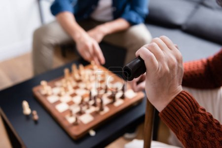 partial view of man with walking stick playing chess with son on blurred background