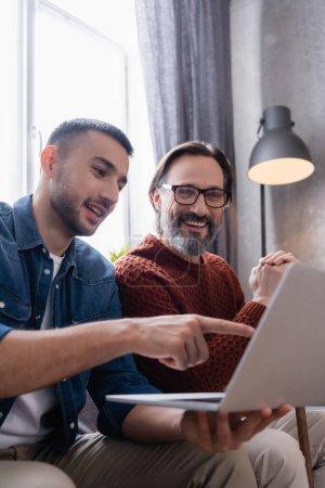 Photo pour Souriant hispanique homme pointant vers ordinateur portable près père gai, premier plan flou - image libre de droit