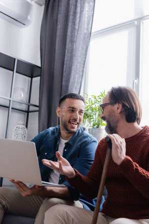 bearded man with walking stick pointing at laptop near excited hispanic son