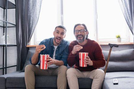 excited interracial father and son laughing while watching comedy and eating popcorn at home