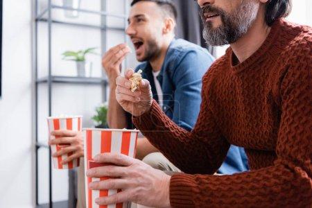 interracial padre e hijo viendo tv mientras comer palomitas de maíz en casa, fondo borroso