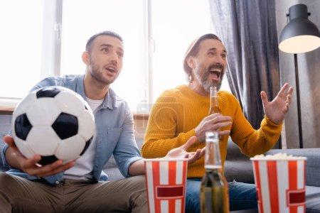 Photo pour Étonné interracial père et fils regarder championnat de football près de bière et pop-corn sur le premier plan flou - image libre de droit