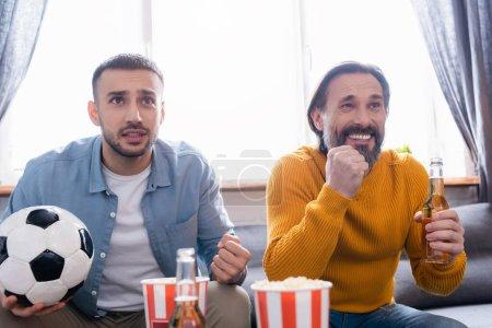 Photo pour Inquiet interracial père et fils regarder match de football avec de la bière et du pop-corn à la maison - image libre de droit