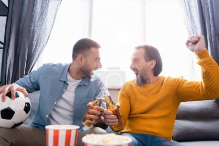 Photo for Excited interracial dad and son clinking bottles of beer while watching football championship at home - Royalty Free Image