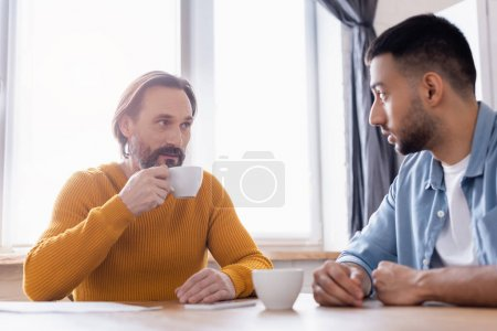 Photo for Bearded man holding coffee cup during conversation with hispanic son in kitchen - Royalty Free Image
