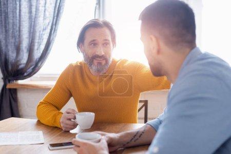 Photo pour Homme barbu souriant regardant son fils pendant la conversation dans la cuisine, au premier plan flou - image libre de droit