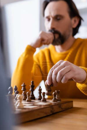 selective focus of thoughtful man playing chess on blurred foreground