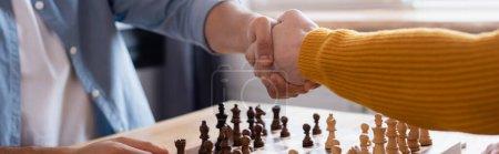 Foto de Vista recortada del padre y el hijo estrechando las manos cerca del tablero de ajedrez sobre fondo borroso, bandera - Imagen libre de derechos