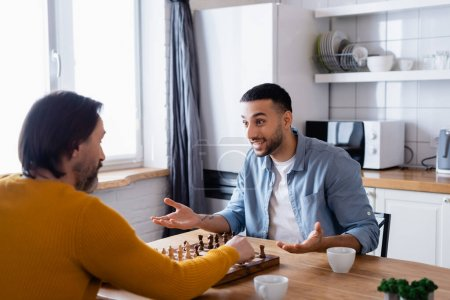 excited hispanic man gesturing while playing chess with father in kitchen