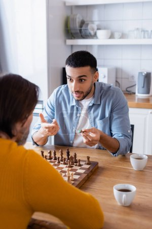 young hispanic man pointing with finger while playing chess with father in kitchen, blurred foreground