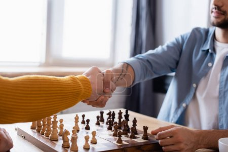 partial view of father and son shaking hands near chessboard at home, blurred background