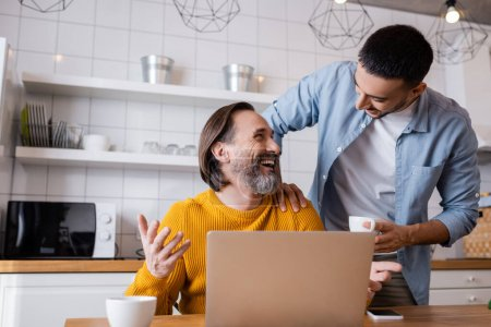 laughing man looking at young hispanic son while sitting near laptop in kitchen
