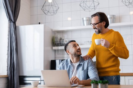 smiling bearded man touching shoulder of happy hispanic son sitting near laptop in kitchen