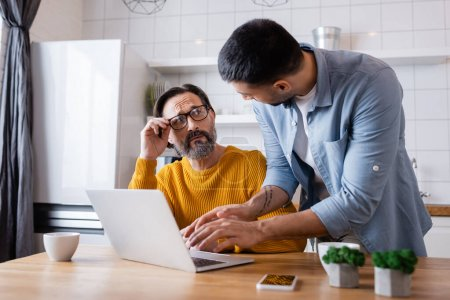 bearded man touching eyeglasses while looking at young hispanic son using laptop, blurred foreground