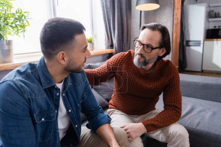 Photo pour Interracial papa et fils regarder l'autre tout en parlant sur canapé à la maison - image libre de droit