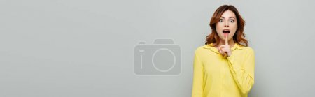 Photo pour Femme étonnée regardant la caméra tout en montrant un geste de silence sur gris, bannière - image libre de droit