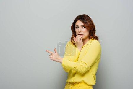 verängstigte Frau hält Hand in Mund, während sie mit dem Finger auf grau zeigt