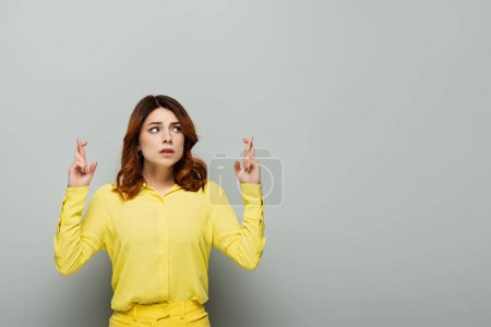 worried woman standing with crossed fingers and looking away on grey