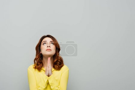 worried woman with wavy hair looking up while showing please gesture isolated on grey