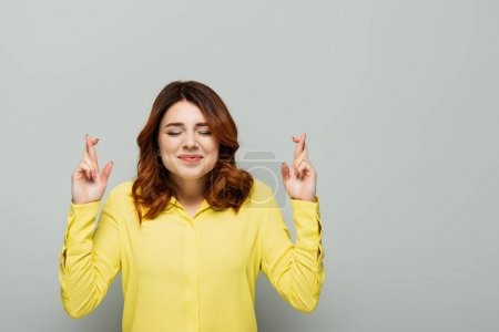 positive woman holding crossed fingers while standing with closed eyes on grey