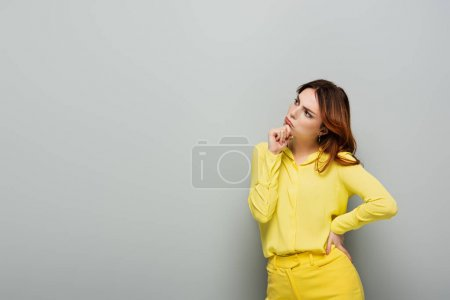 Photo for Pensive woman in yellow clothes standing with hand on hip on grey - Royalty Free Image