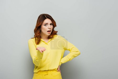 shocked woman pointing with hand while standing with hand on hip on grey