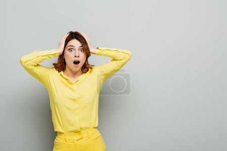 Photo for Shocked woman touching head while standing with open mouth on grey - Royalty Free Image