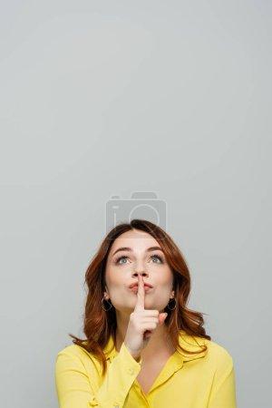 Photo pour Femme positive levant les yeux tout en montrant shh geste isolé sur gris - image libre de droit