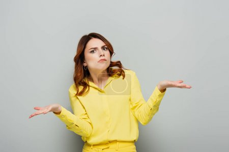 confused woman looking at camera while showing shrug gesture on grey