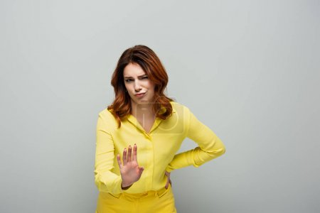 displeased woman looking at camera while showing stop gesture on grey