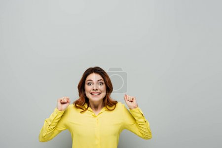 Photo for Cheerful woman smiling at camera while standing with clenched fists on grey - Royalty Free Image