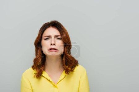 Photo pour Découragée femme regardant caméra et grimaçant isolé sur gris - image libre de droit