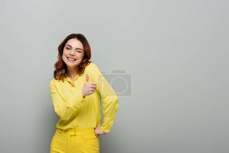 Photo for Happy woman winking and showing thumb up while standing with hand on hip on grey - Royalty Free Image