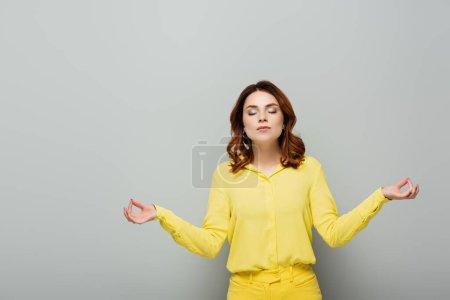 Photo pour Jeune femme aux cheveux bouclés méditant les yeux fermés sur le gris - image libre de droit