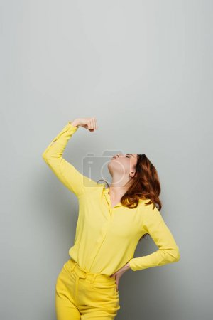 Photo for Woman in yellow shirt demonstrating strength on grey - Royalty Free Image