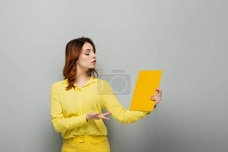 Photo for Arrogant woman in yellow blouse pointing at notebook on grey - Royalty Free Image
