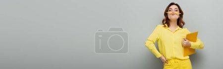 Photo pour Femme avec la main sur la hanche et crayon entre le nez et les lèvres regardant caméra sur gris, bannière - image libre de droit