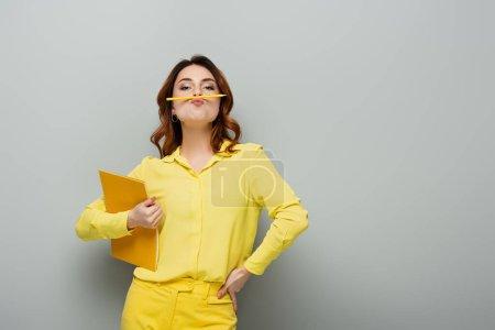 Photo pour Femme bouclée avec crayon entre le nez et les lèvres posant avec la main sur la hanche sur gris - image libre de droit