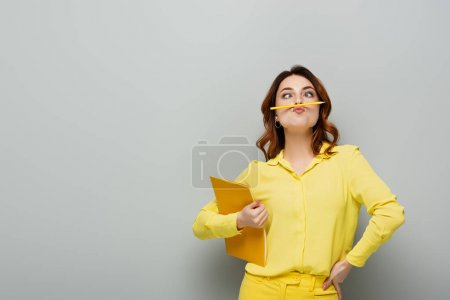 Photo pour Femme gaie avec crayon entre le nez et les lèvres posant avec cahier sur gris - image libre de droit