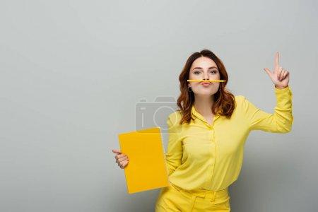 Photo pour Femme avec crayon entre le nez et les lèvres pointant vers le haut avec le doigt sur gris - image libre de droit