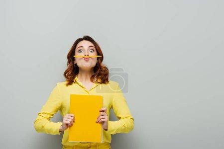 Photo pour Femme gaie avec crayon entre les lèvres et le nez en regardant la caméra sur gris - image libre de droit
