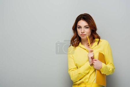 Photo pour Femme réfléchie avec crayon et cahier regardant la caméra sur gris - image libre de droit