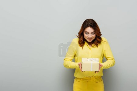 Photo for Pleased woman in yellow clothes holding gift box on grey - Royalty Free Image