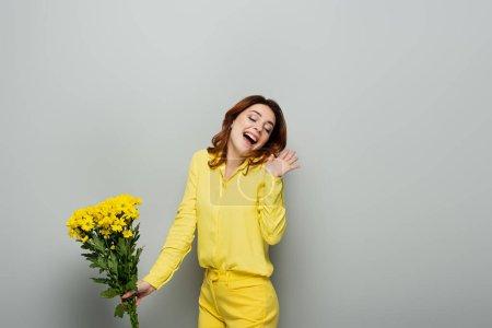 Photo pour Femme étonnante avec les cheveux ondulés et les yeux fermés tenant des fleurs jaunes sur gris - image libre de droit