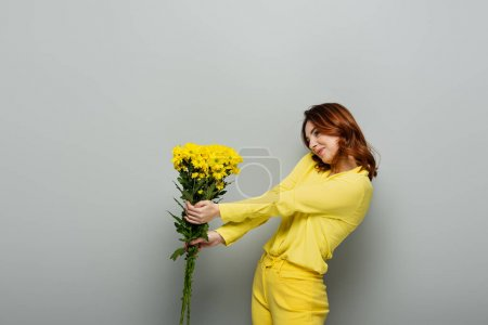cheerful woman with curly hair holding yellow flowers on grey