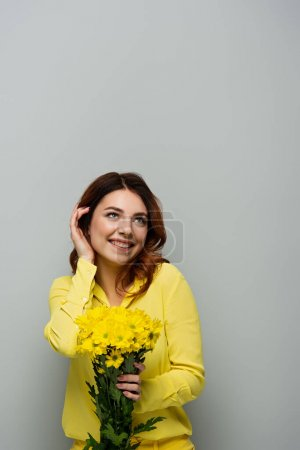 joyful woman fixing curly hair and looking away while holding yellow flowers on grey