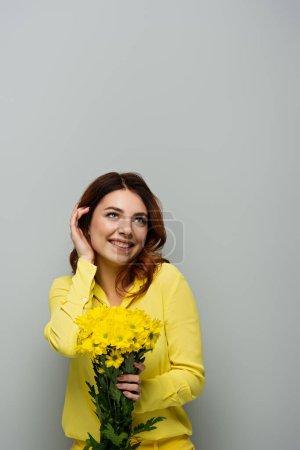 Photo pour Femme joyeuse fixant les cheveux bouclés et regardant loin tout en tenant des fleurs jaunes sur gris - image libre de droit