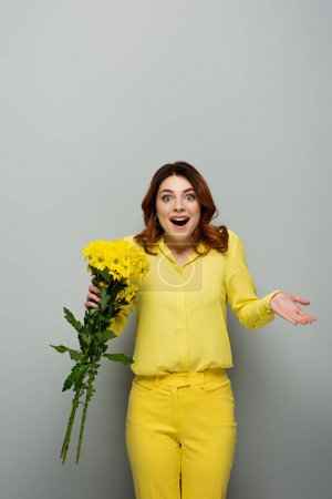 astonished woman holding yellow flowers while standing with open mouth on grey