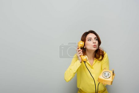 surprised woman pouting lips while talking on vintage telephone on grey