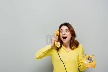 amazed woman looking away while talking on retro telephone on grey